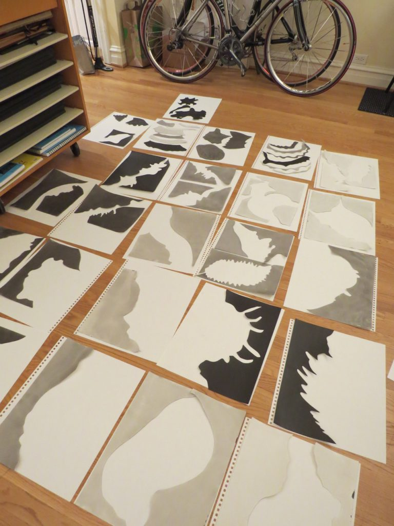 SORTING COLORED SHAPES - The shapes get wrinkled and curly as a result of the sumi-e ink application and the drying process. The final step is making sure they are pressed flat. The pieces are layered between sheets of paper that are sandwiched between dense sheets of cardboard. Big old, art books are quite useful as weights. The paper sandwich is pressed for a couple days. Then the final sort is done.